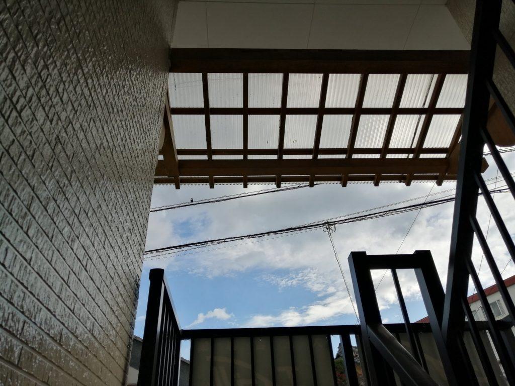 階段の踊り場で雨に濡れないようにと後付けされたタキロン製の屋根