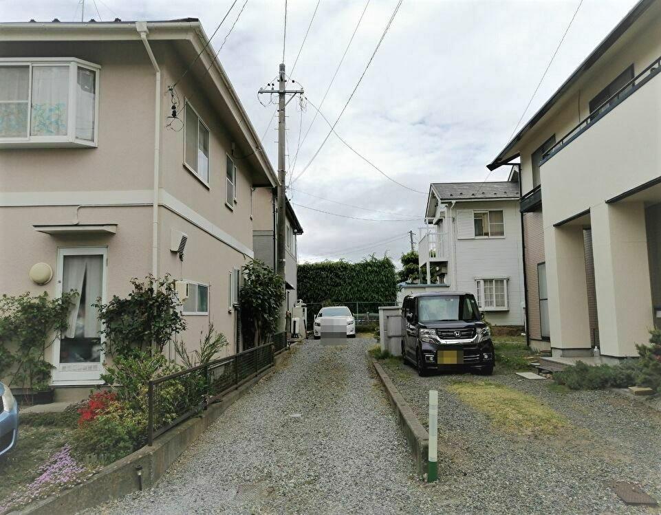 敷地延長で通路奥に駐車スペースと住宅がある旗竿地