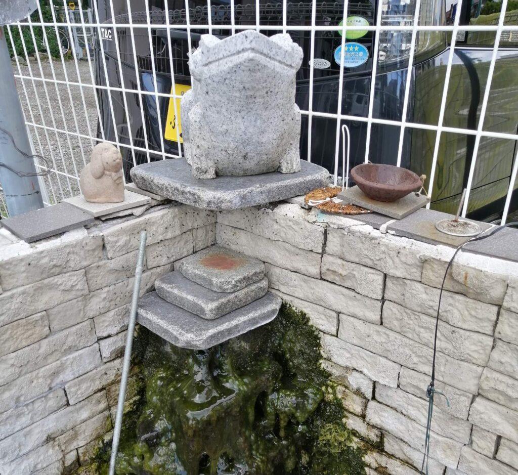 かえるの石像から水が湧いている街角のオブジェ