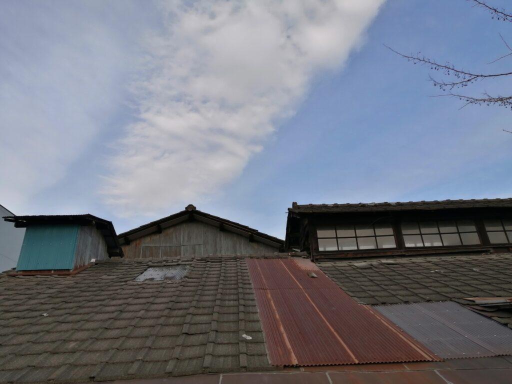 トタン屋根で補修された瓦屋根