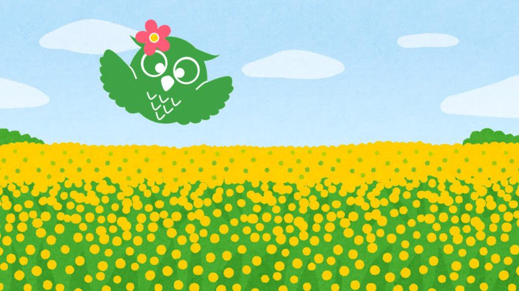 花飾りをつけたあいしーちゃんが花畑の上を飛んでいるイラスト